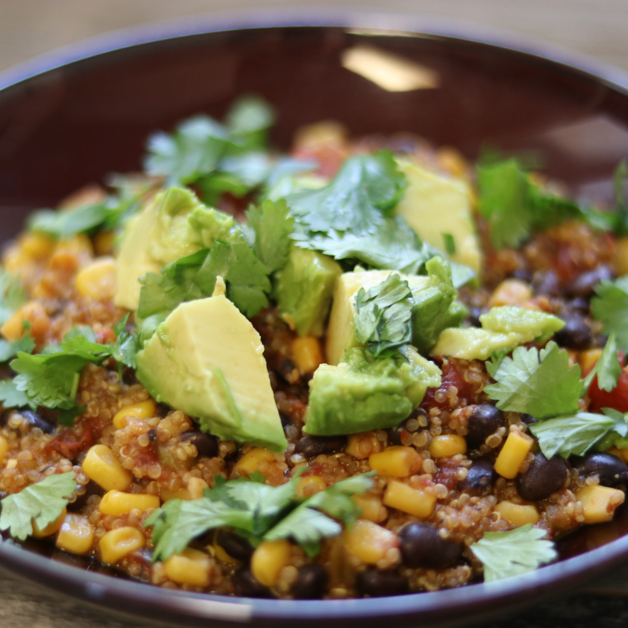 quinoa and corn topped with avocado and cilantro