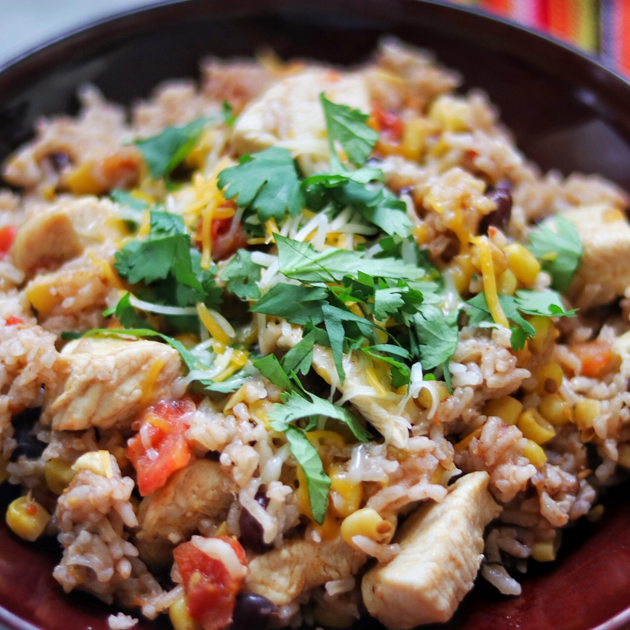 Instant Pot® Mexican Chicken and Rice Bowl topped with cheese and cilantro