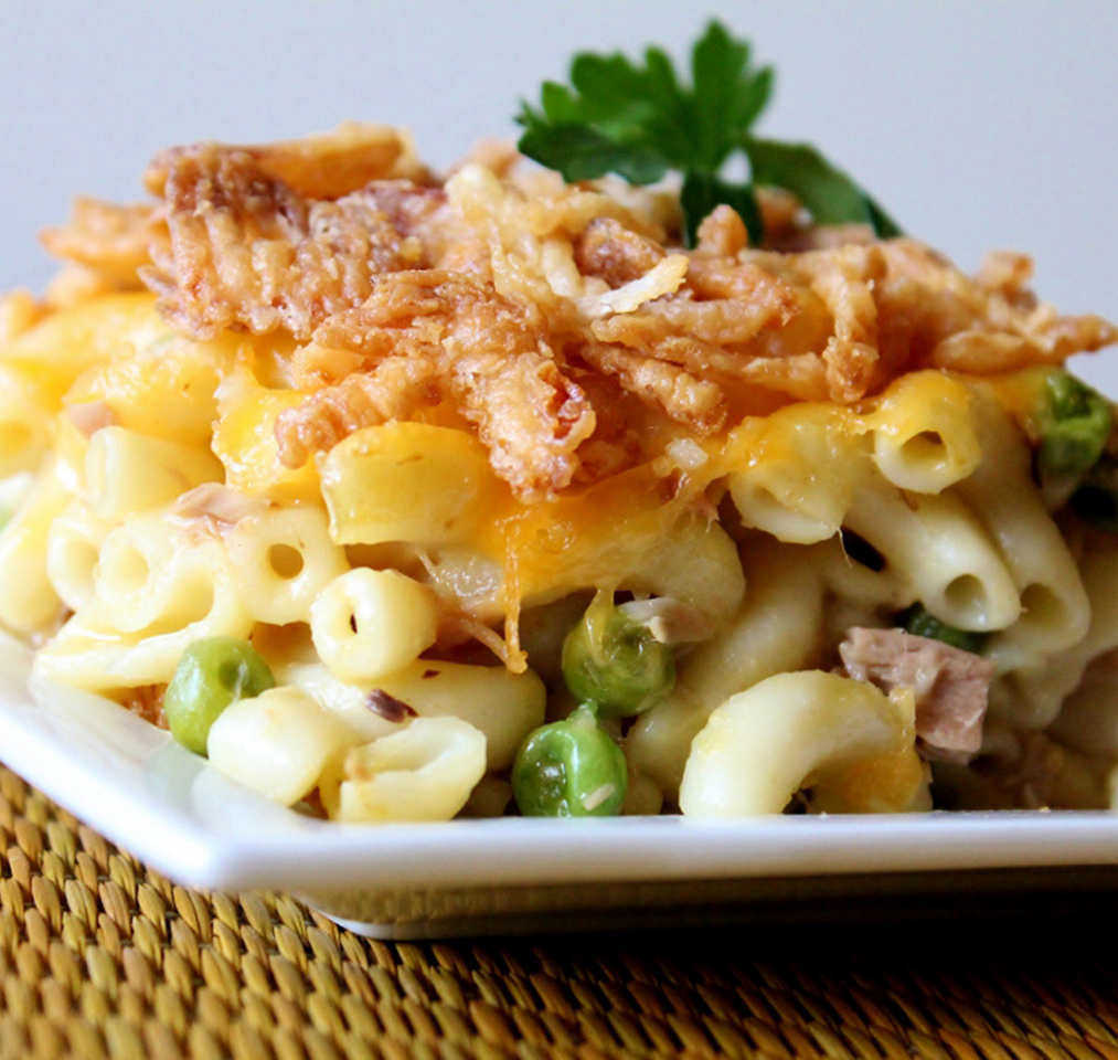 Serving of tuna macaroni casserole with peas and a crispy cheesy topping