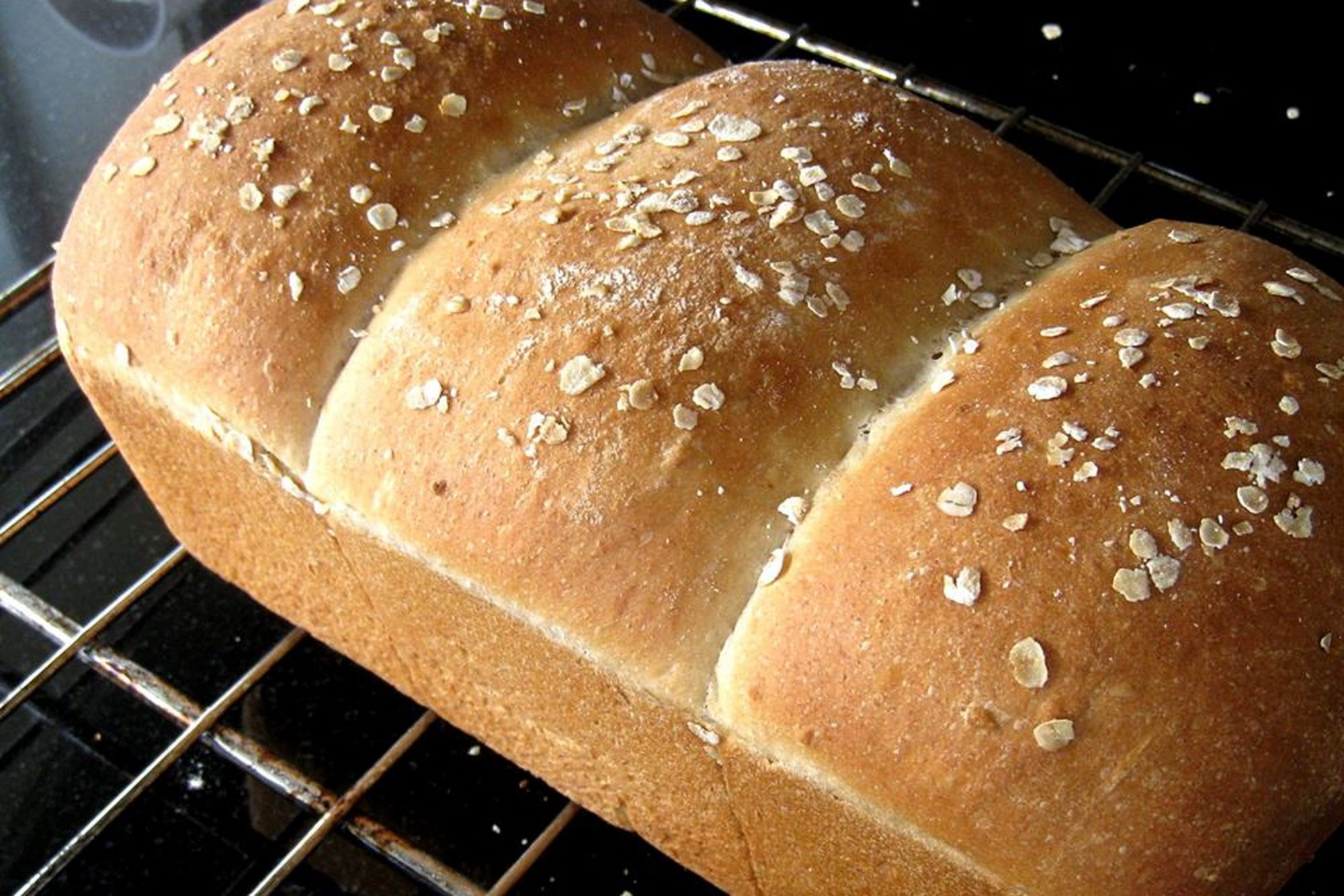 Light Oat Bread with delicate oatmeal topping on cooling rack