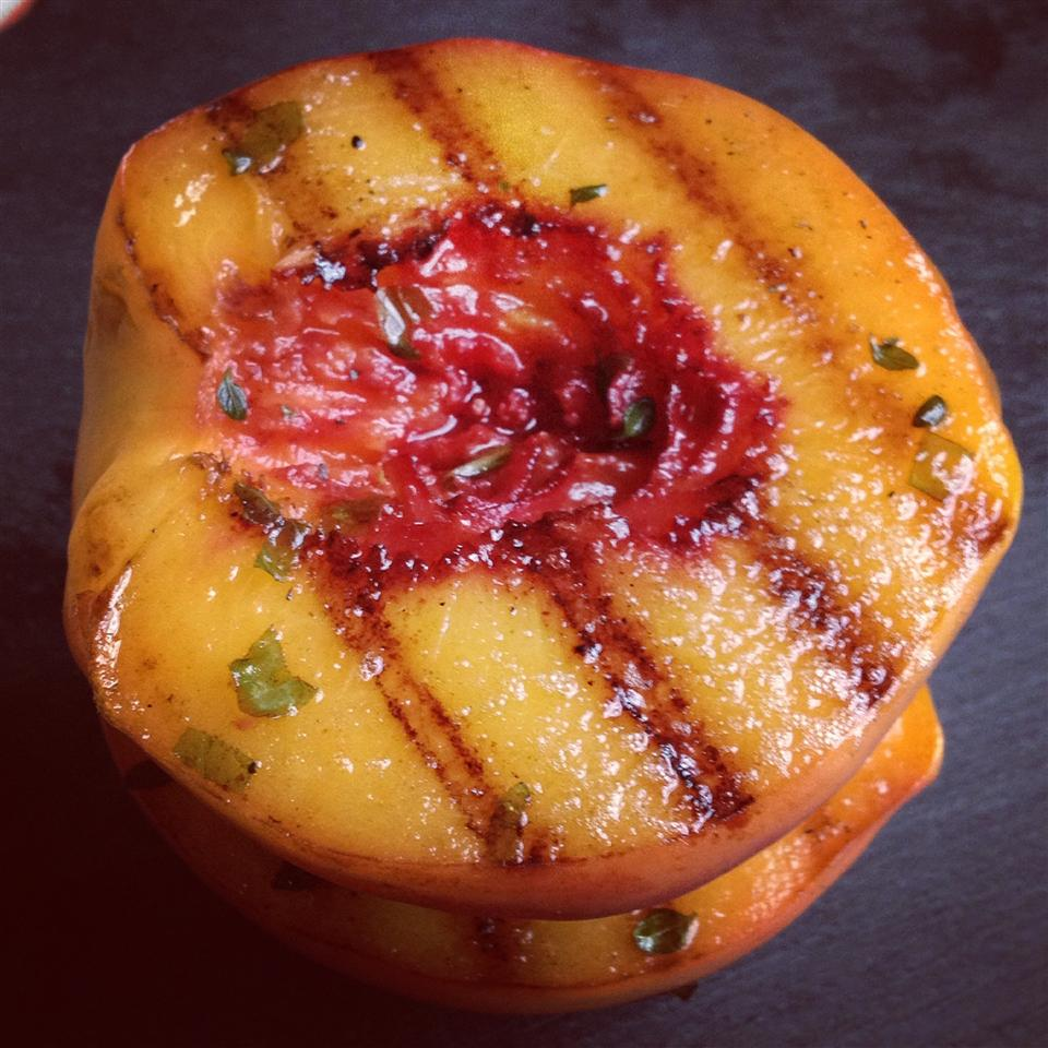 closeup of a juicy-looking peach half with grill marks