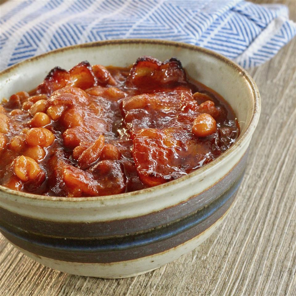 A ceramic bowl filled with baked beans, garnished with bacon slices