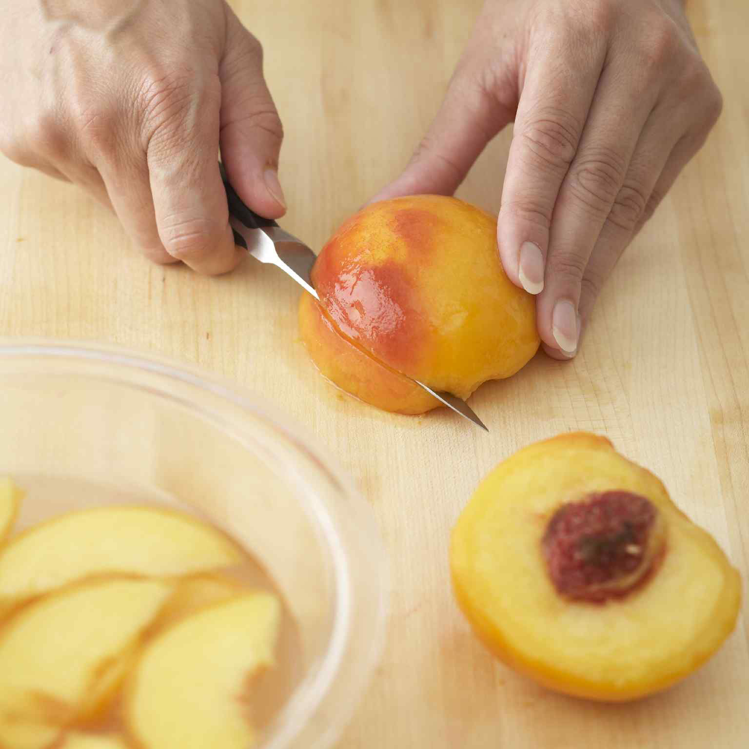 Person slicing peeled peach