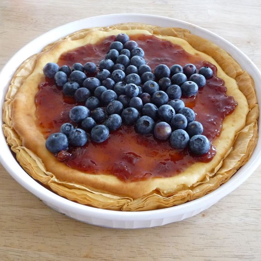 Pie in a white dish decorated with a blueberry star