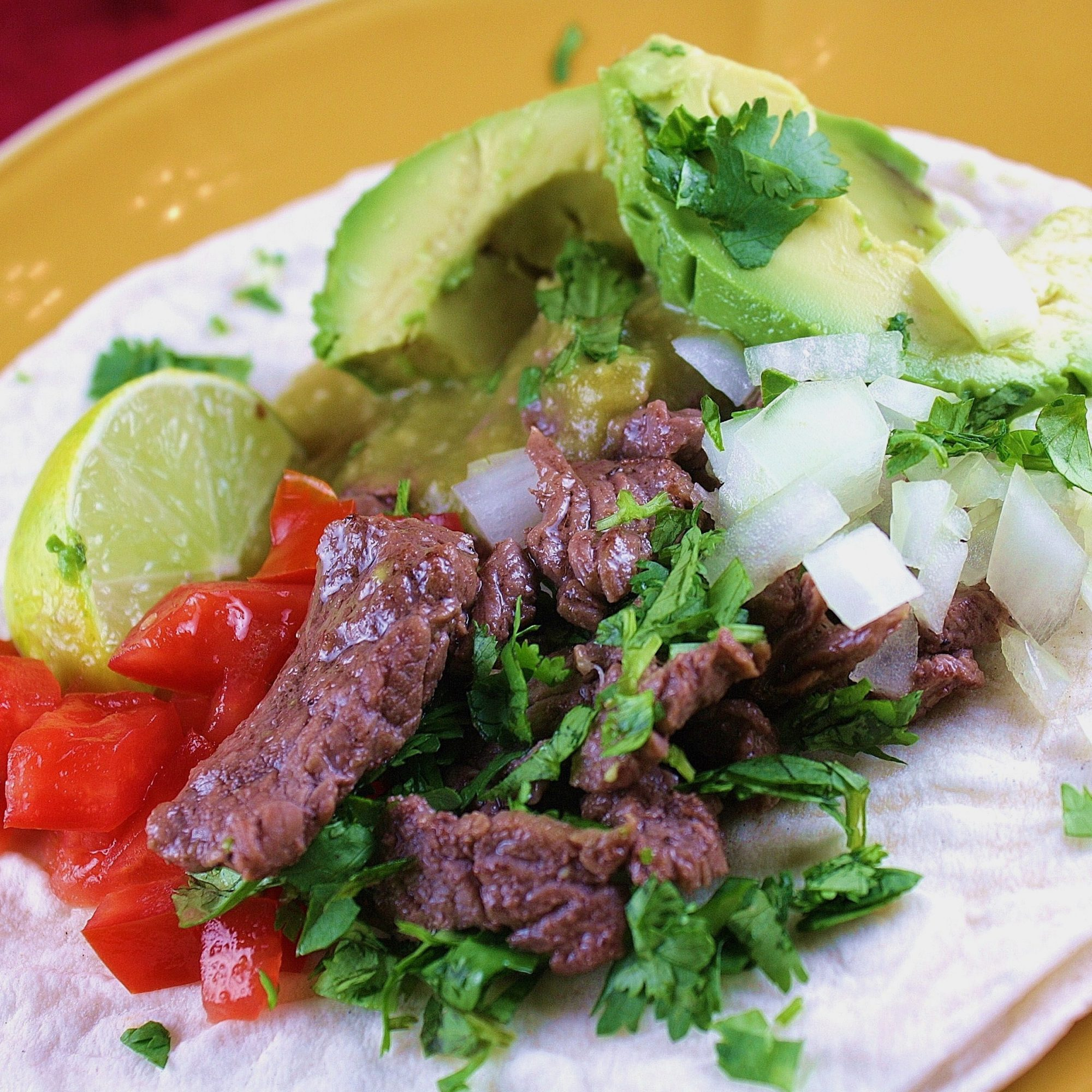 closeup of flour tortillas topped with beef strips, chopped onion, cilantro, avocado, and a lime wedge