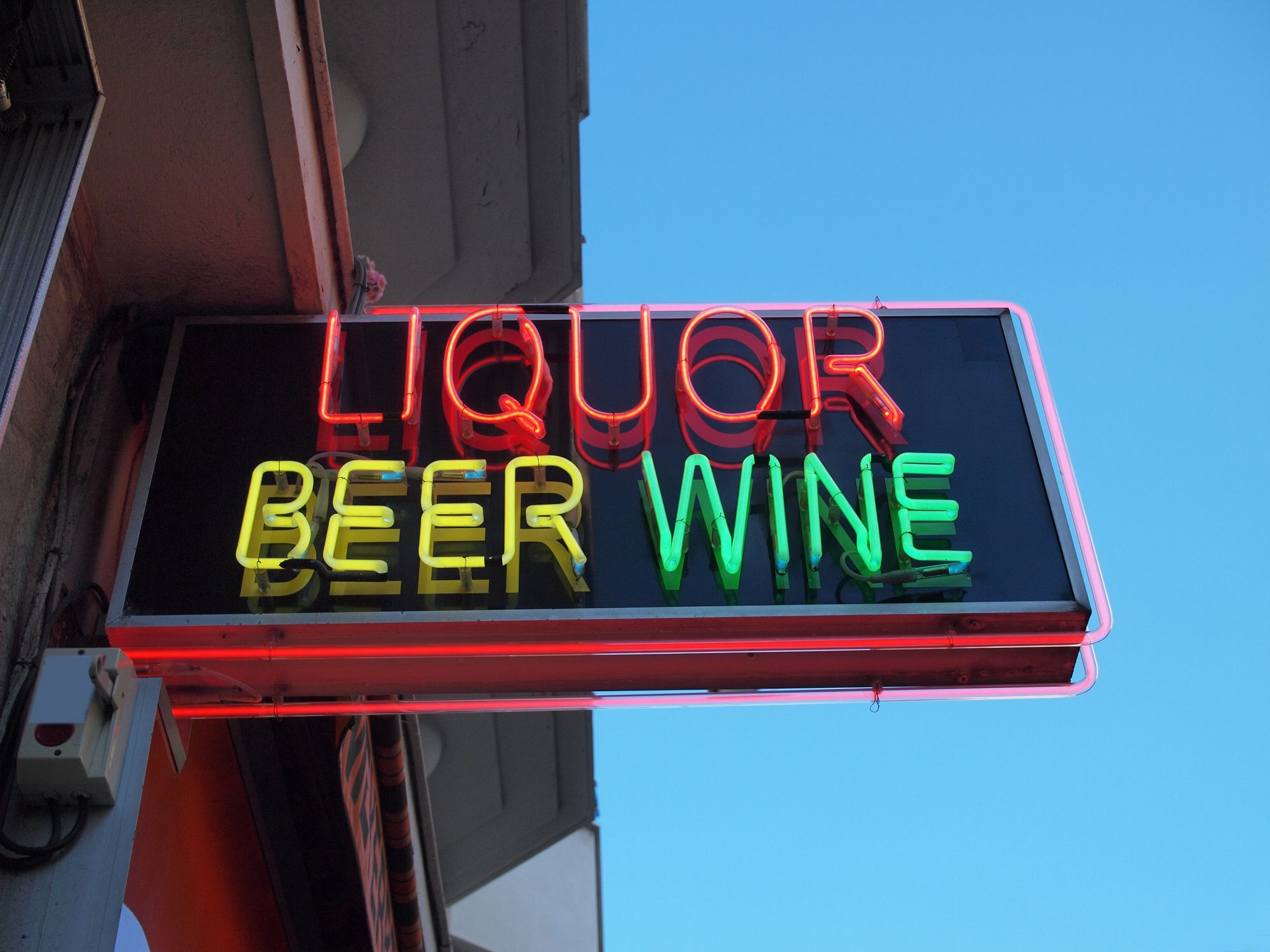 A neon sign on a store selling alcohol. The words, liquor, beer and wine glowing in bright neon. A clear blue sky in the background.