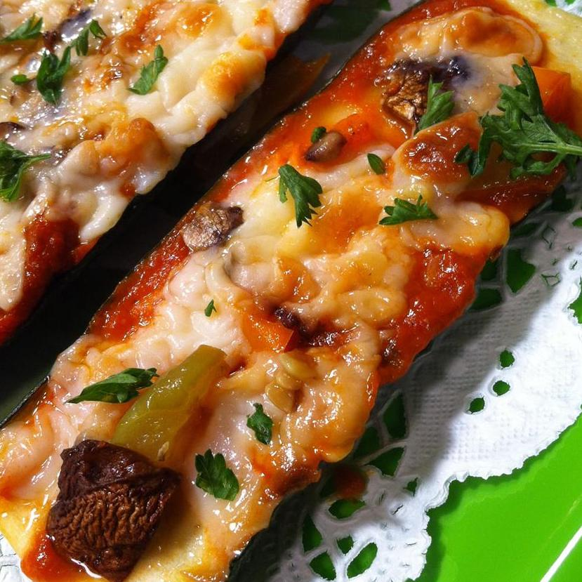 zucchini sliced in half with red sauce and cheese