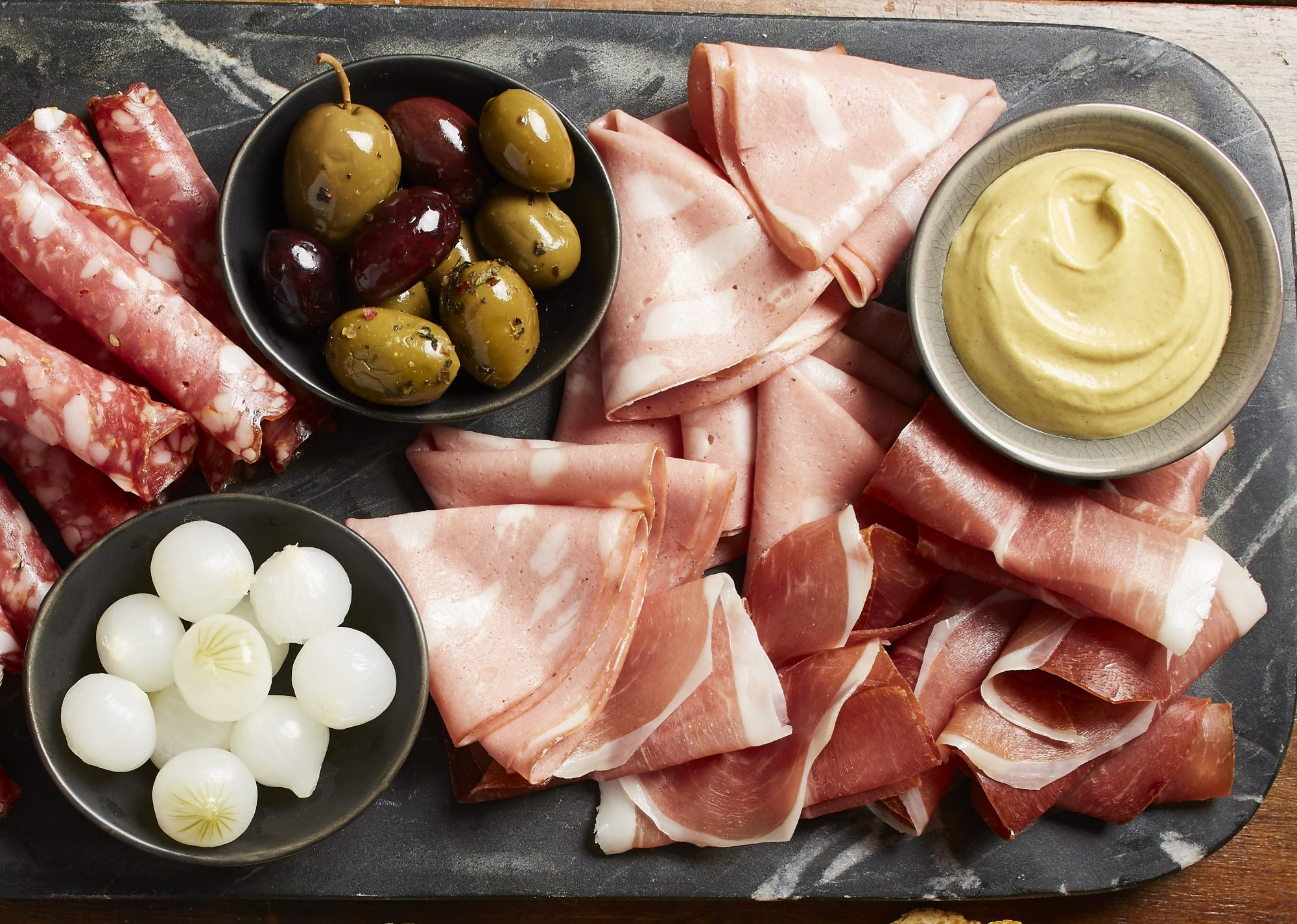 Charcuterie board with meats, cheese, olives, and mustard