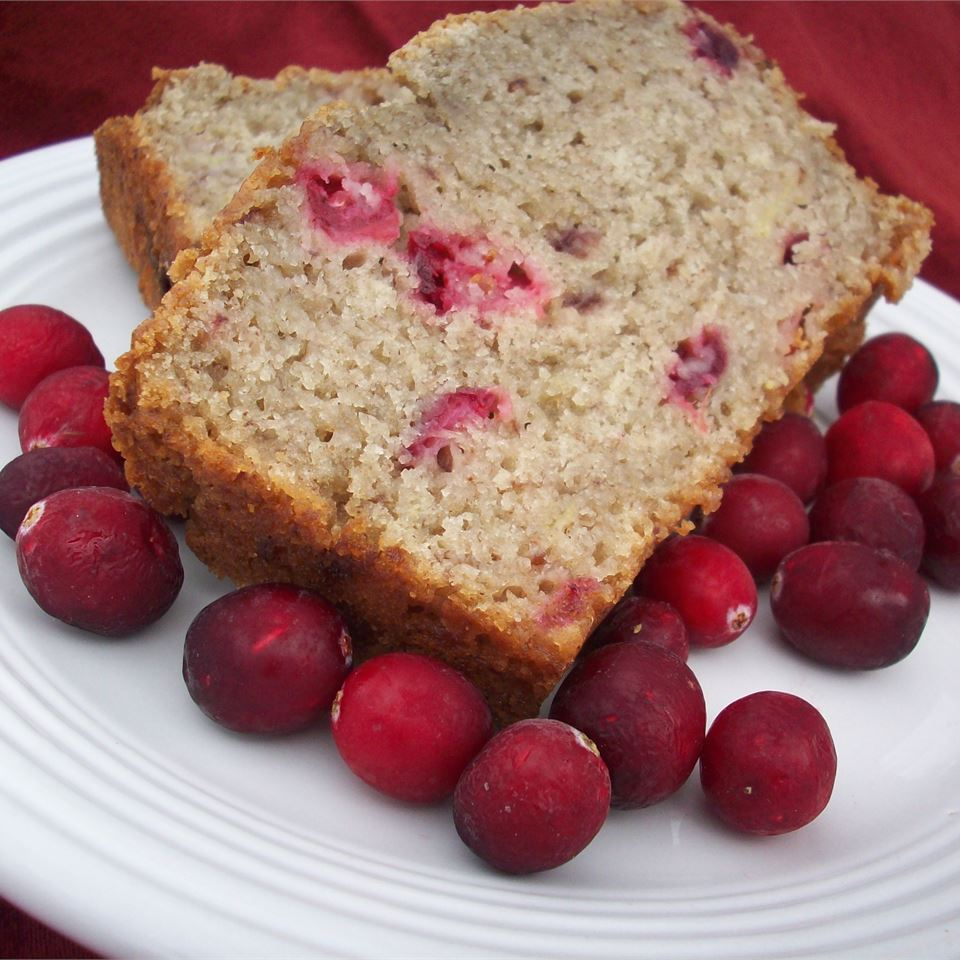 Slice of quick bread on a plate garnished with fresh cranberries