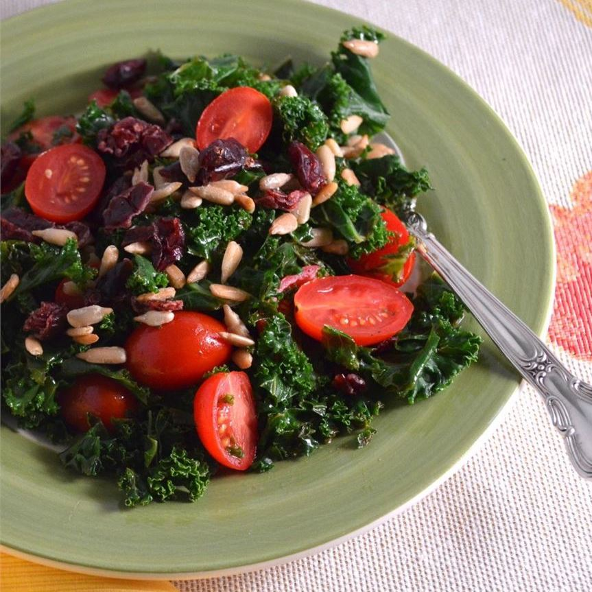 a salad of chopped kale, grape tomatoes, and sunflower seeds on a pale green plate