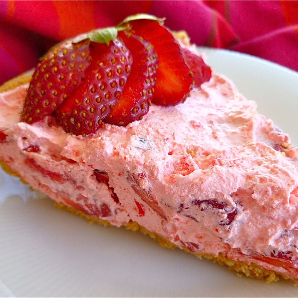 Fluffy Strawberry Pie on a plate with sliced strawberries
