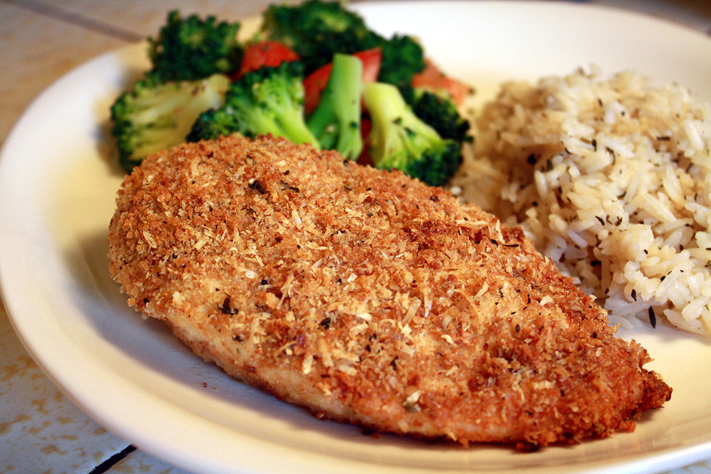 a breaded baked chicken breast on a dinner plate with rice pilaf and broccoli in the background