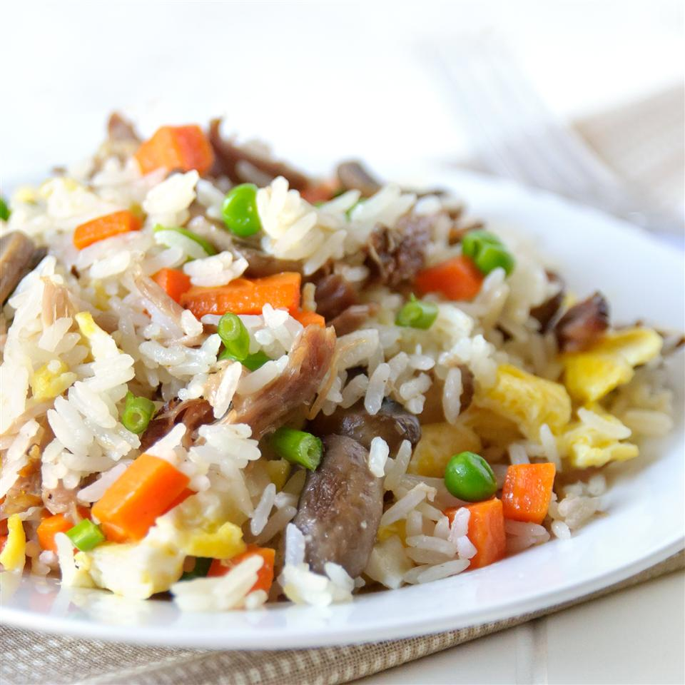 side view of a serving of fried rice with pork, peasn, and carrots on a white plate