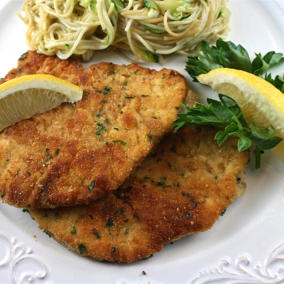 breaded fried chicken breast cutlets garnished with lemon wedges on a plate with spaghetti in the background