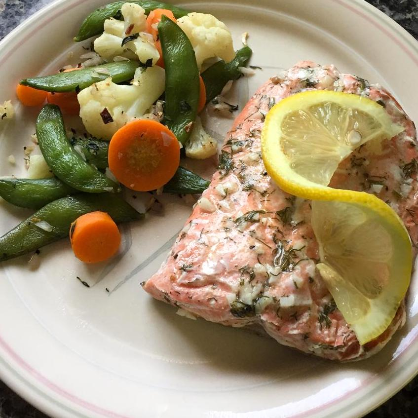 salmon with dill and lemon garnish on a plate with veggies