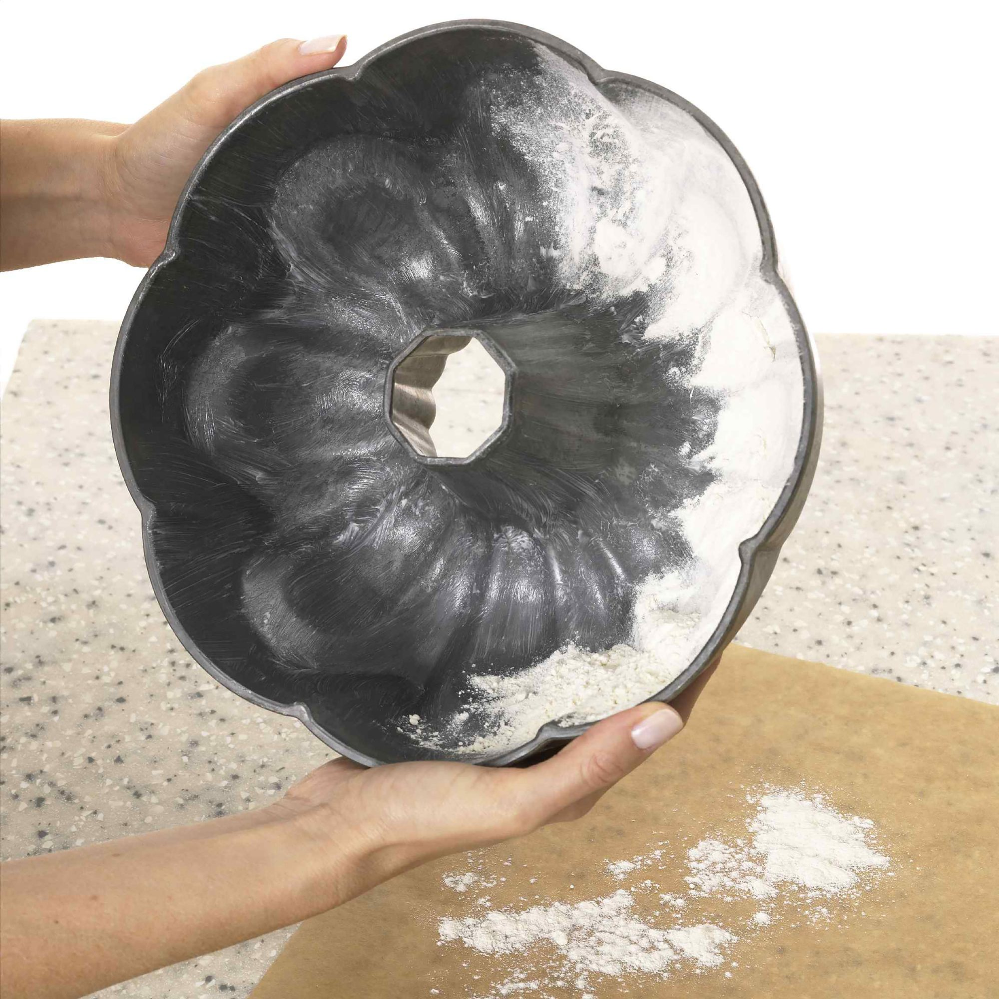 person flouring bundt pan