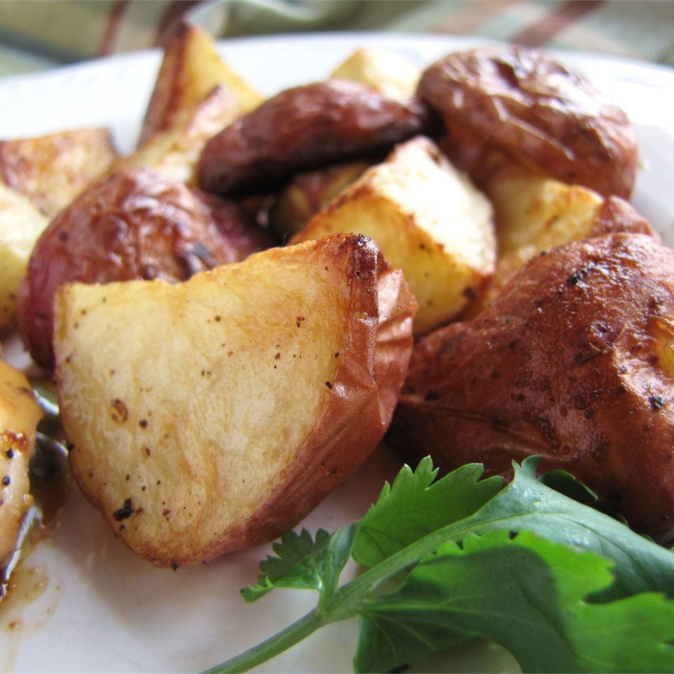 Roasted New Red Potatoes with garnish on a white plate