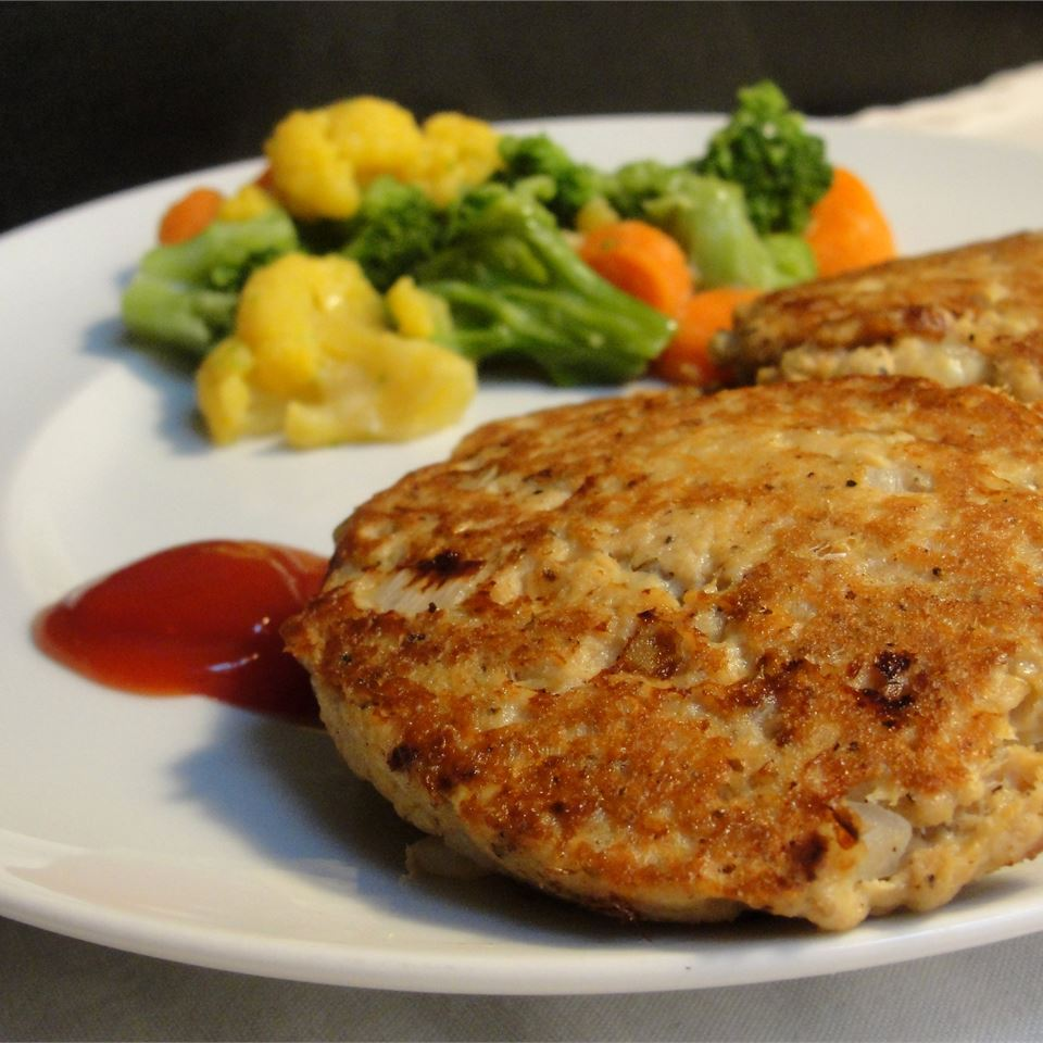 salmon cakes on a white plate with mixed vegetables