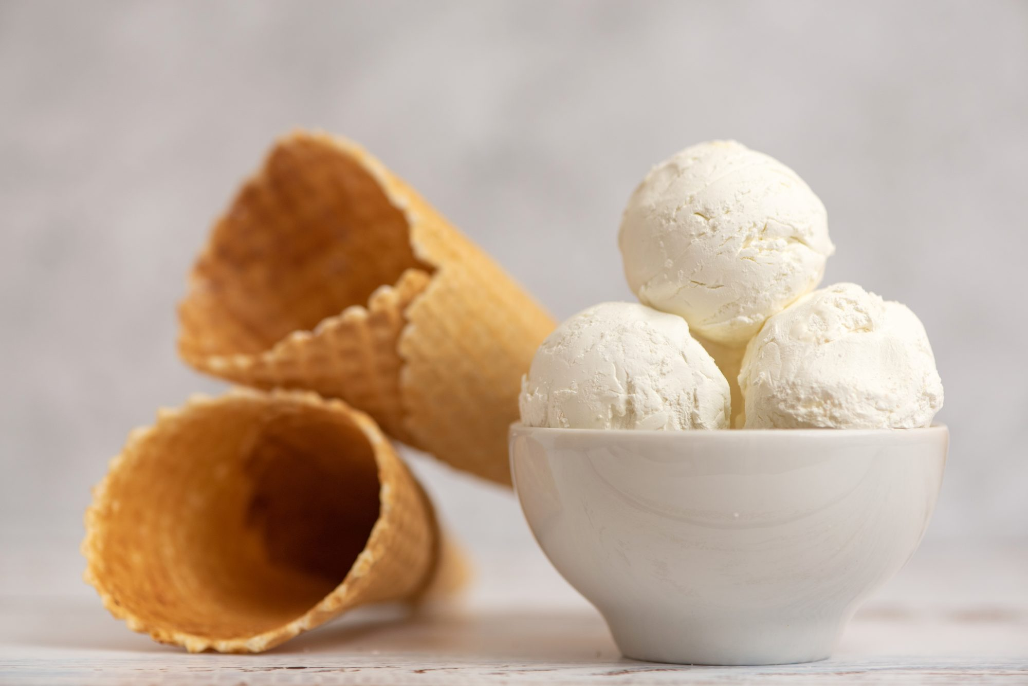 Bowl of vanilla ice cream and waffle cones on light background. Side view