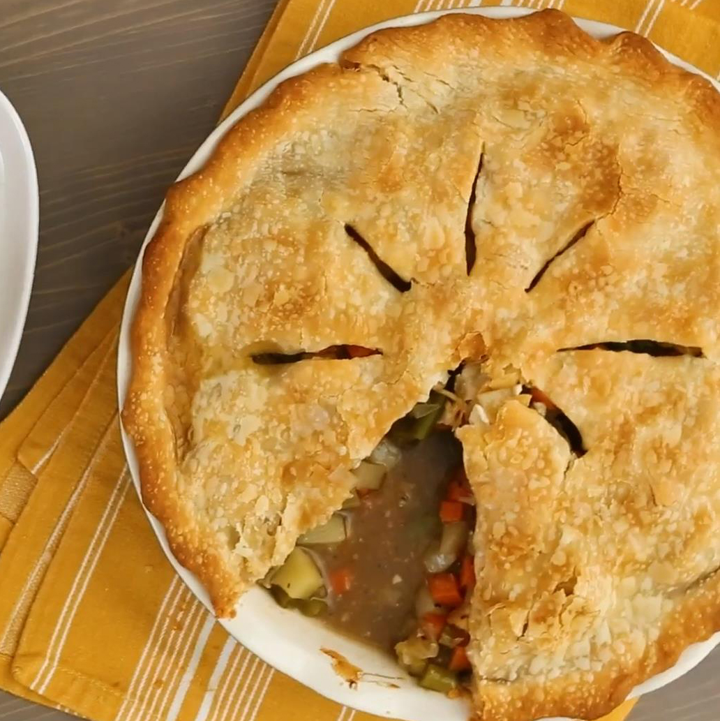 a top-down view of a two-crust pie with a slice cut out