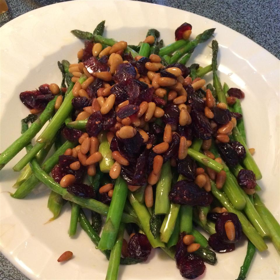 Asparagus with Cranberries and Pine Nuts on a white plate