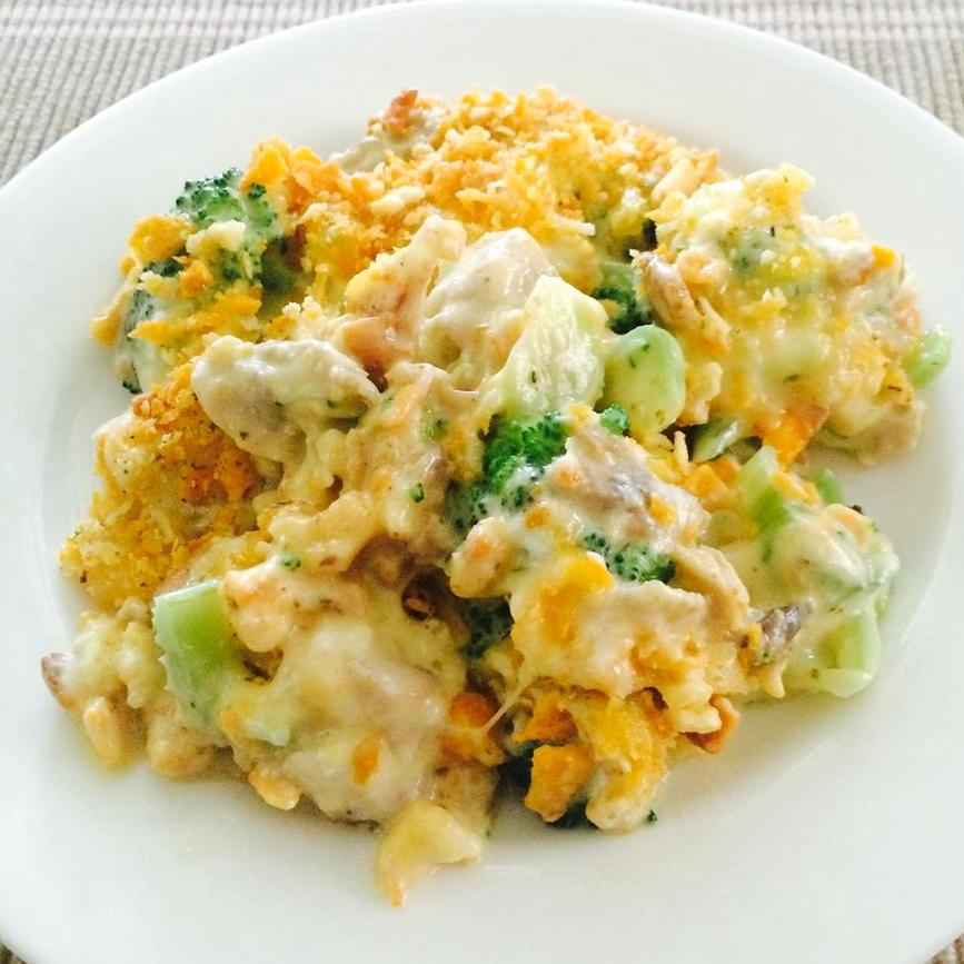A serving of casserole with chicken, cheddar, and broccoli on a white plate