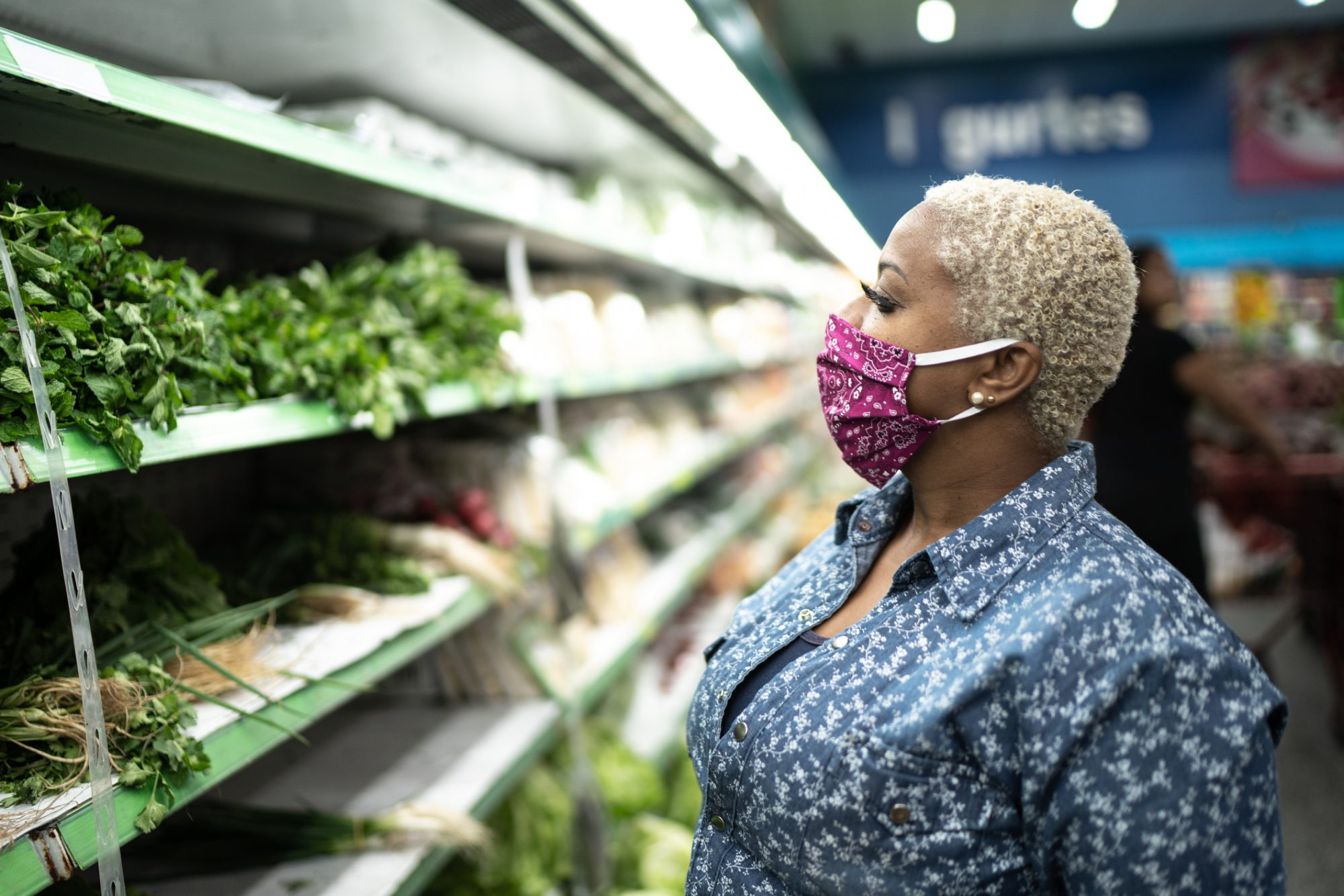 Woman with face mask shopping at supermarket