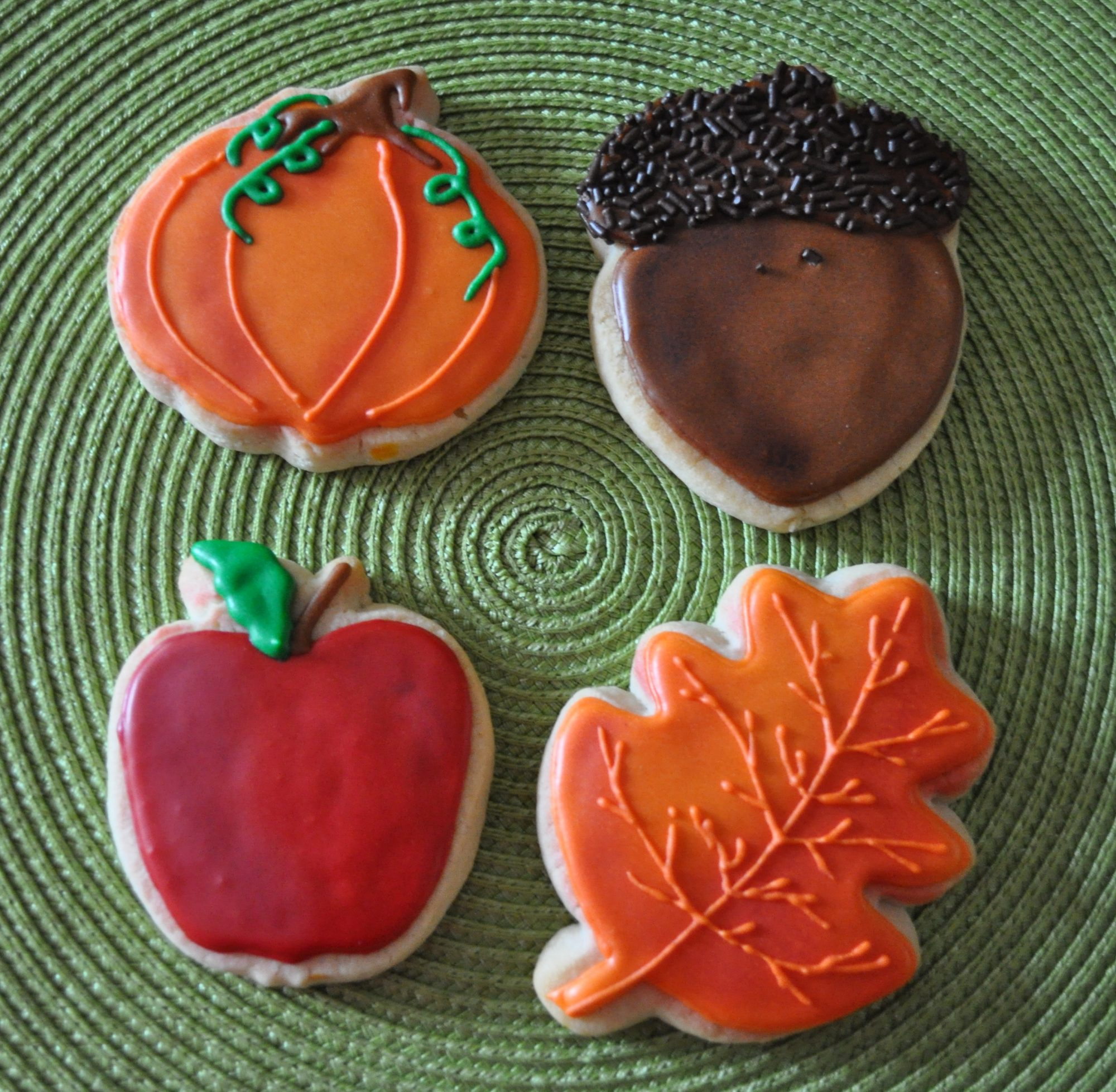 Fall motif cookies on a green placemat: an orange pumpkin, a brown acorn with sprinkles on its cap, a red apple with green leaf, and an orange oak leaf
