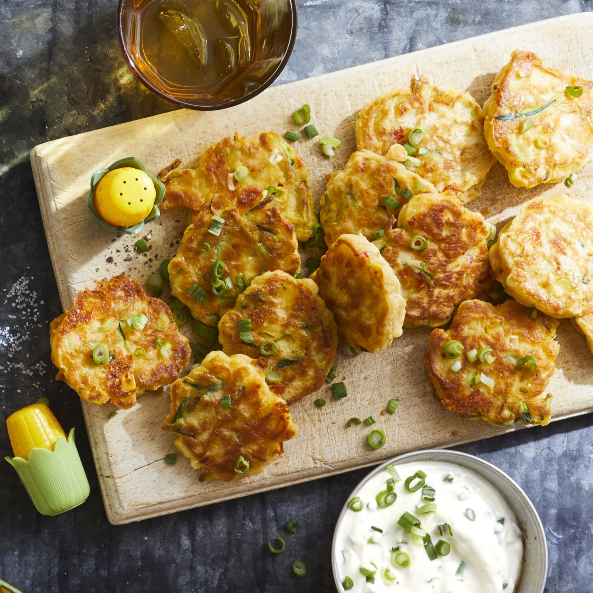 Zucchini Corn Fritters on a wooden board beside bowl of dipping sauce