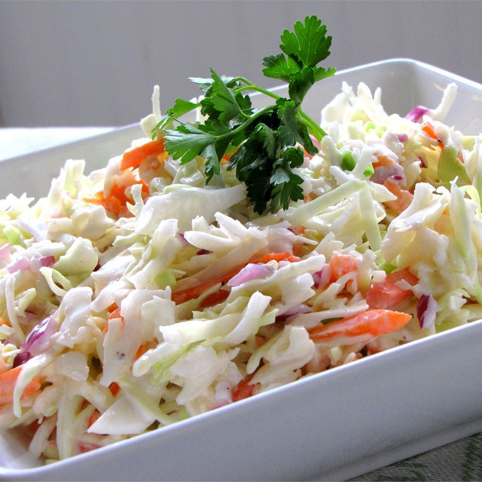 A white bowl filled with creamy coleslaw made with shredded carrots and green cabbage