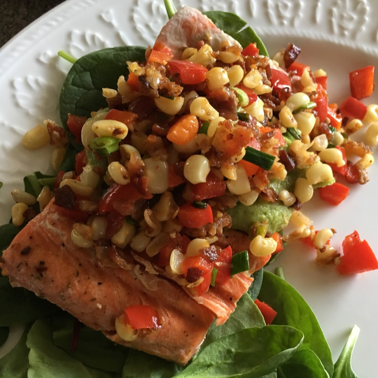 Grilled Salmon with Bacon and Corn Relish recipe served over spinach on a white plate