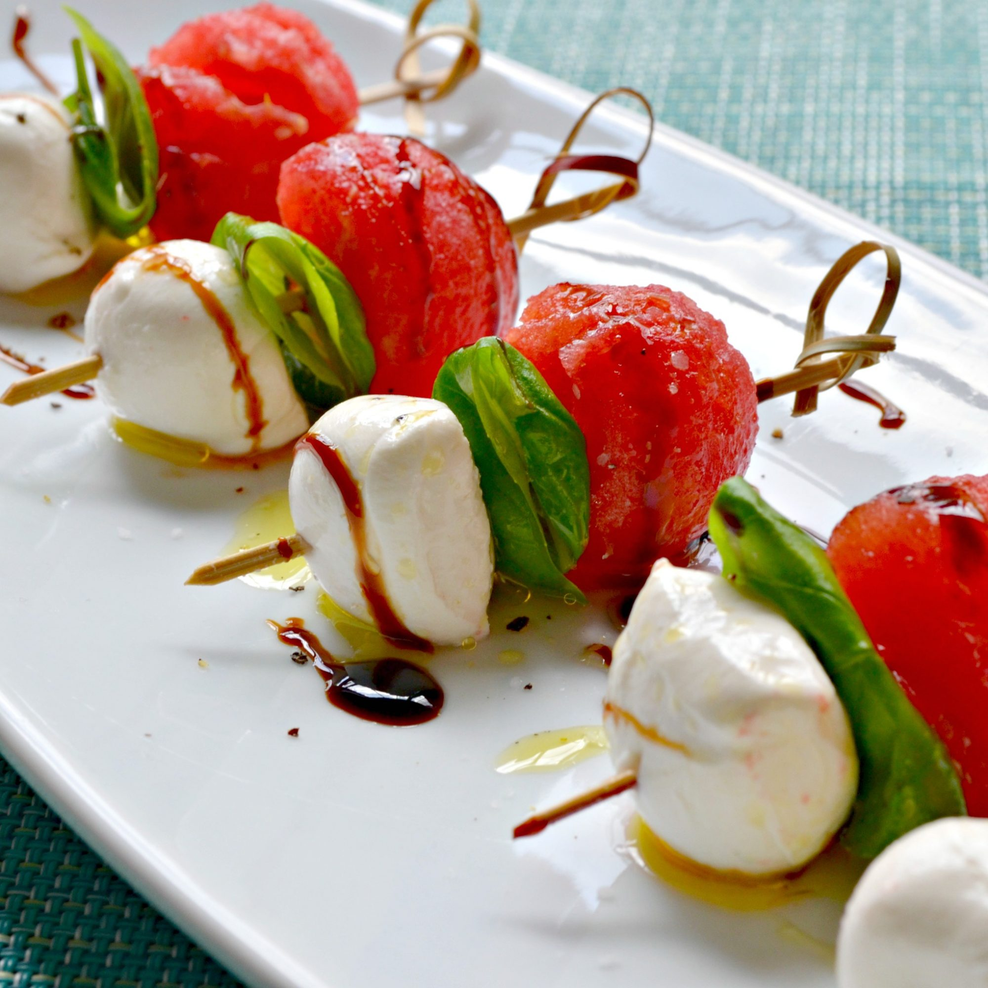 a row of fancy toothpicks holding fresh mozzarella balls, basil leaves, and watermelon balls on a white tray, with a drizzle of balsamic vinegar