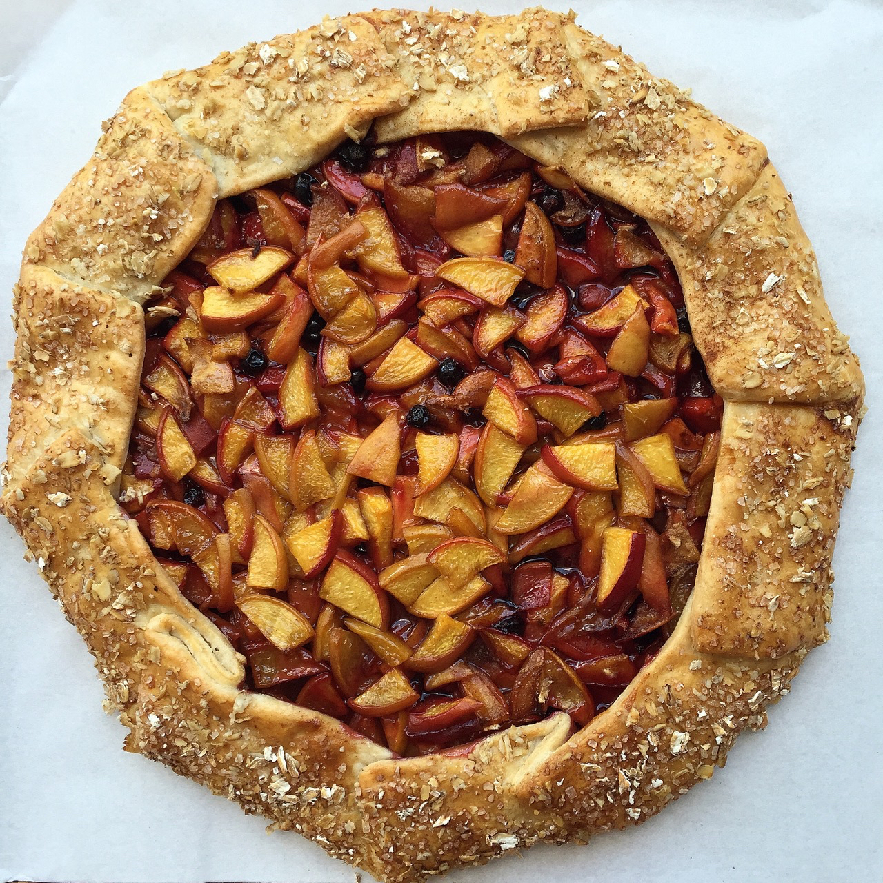 Vanilla-kissed peaches are piled atop a homemade pie crust. To make it extra pretty, brush the folded crust with egg wash and sprinkle with coarse sugar before baking.