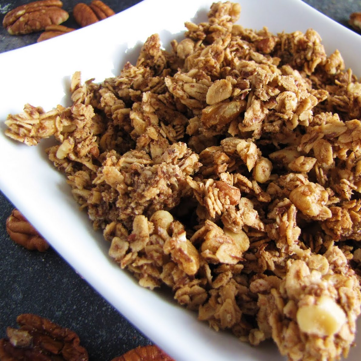 A square white bowl filled with homemade granola