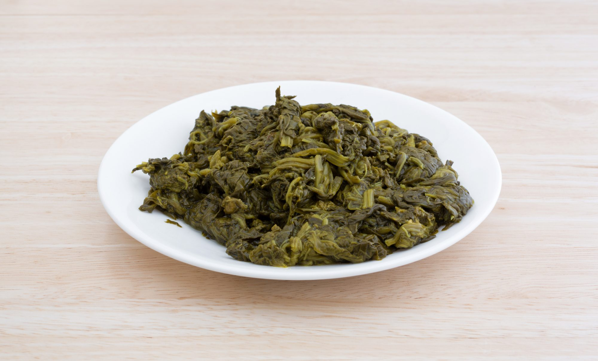 Serving of canned spinach on a white plate