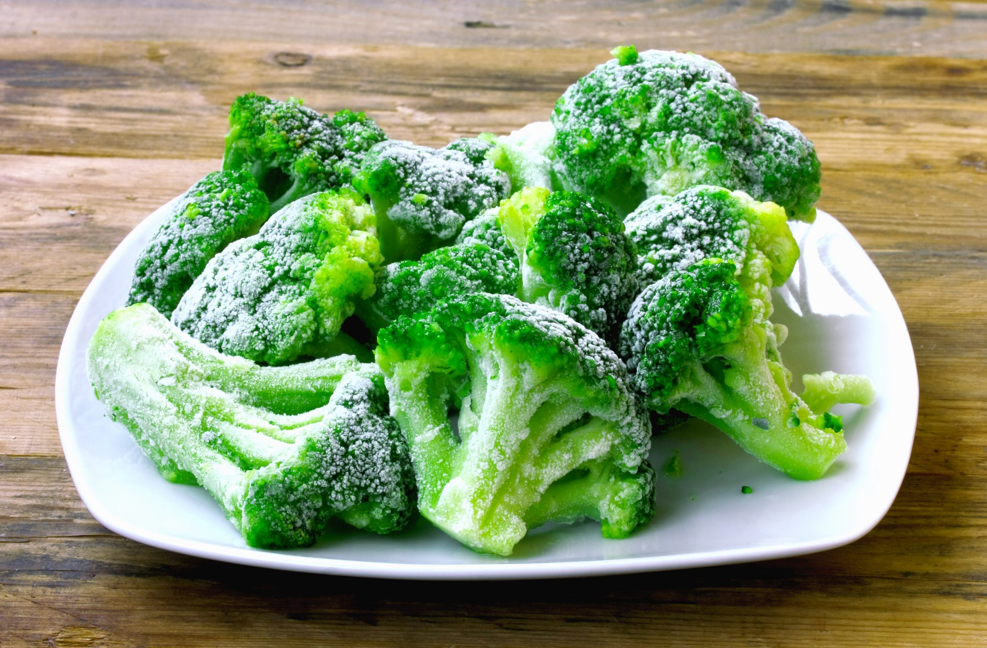 Fresh frozen broccoli on white plate, wooden table, healthy diet food, closeup