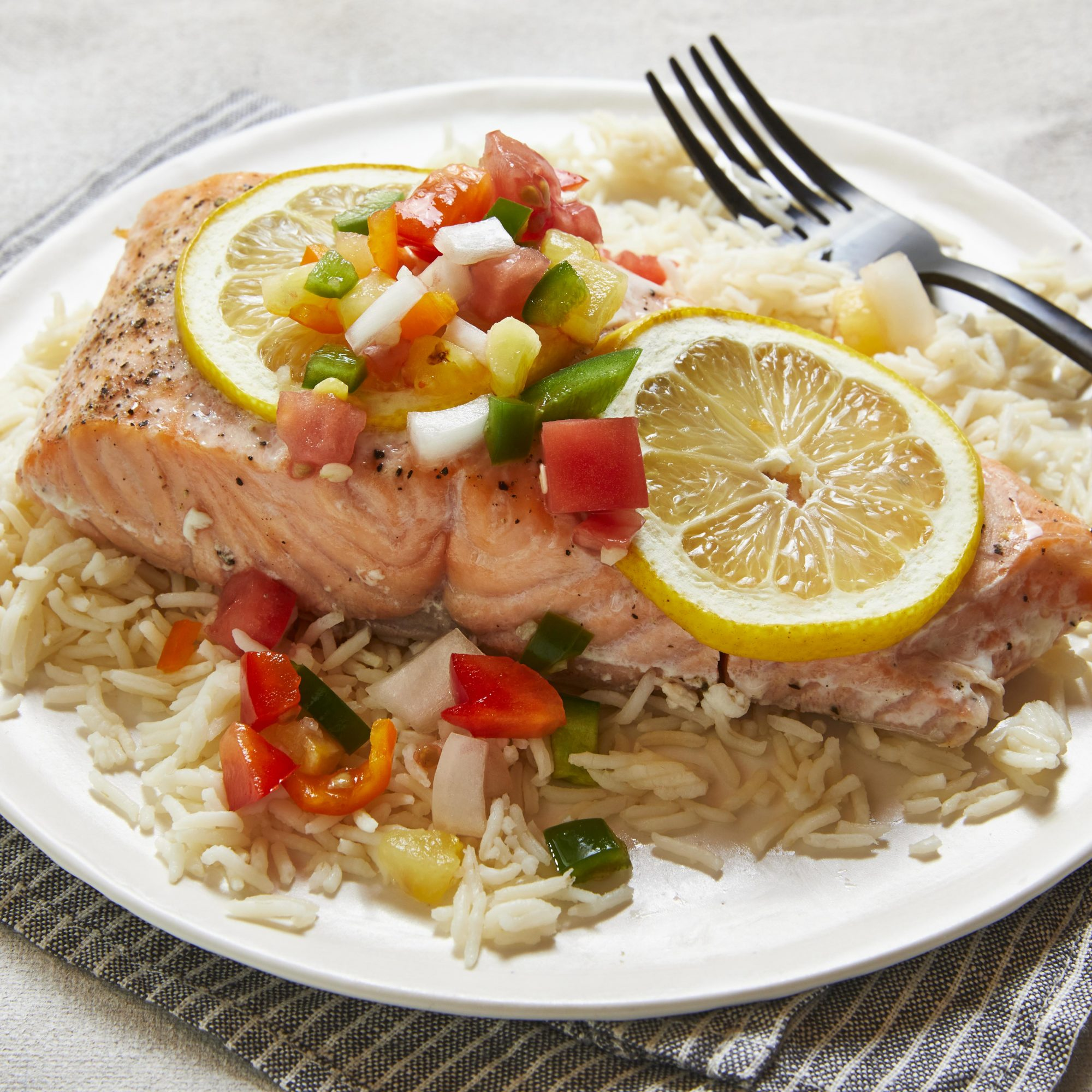 Close-up on salmon fillet with fruit salsa, over rice.