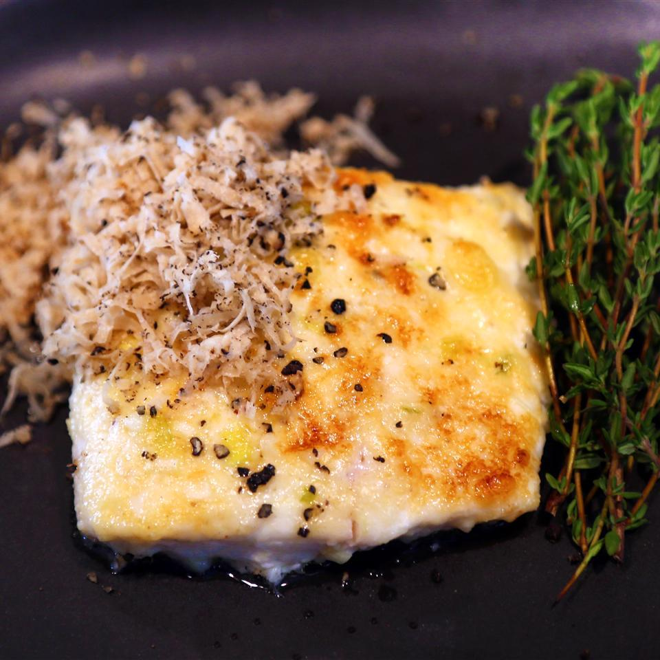 halibut on a gray plate with rosemary garnish on the side