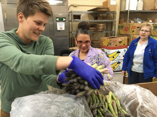 In this pre-COVID photo, Christina Barkel (far left), a lead coordinator of Groundwork's Local Food Relief Fund, packages asparagus at the Goodwill Northern Michigan Food Rescue warehouse.