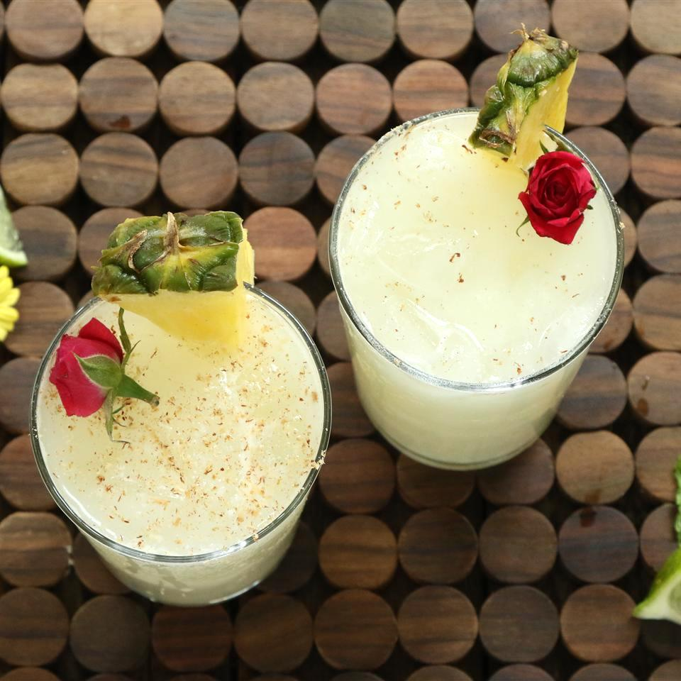 tiki cocktails garnished with pineapple slices and mini roses
