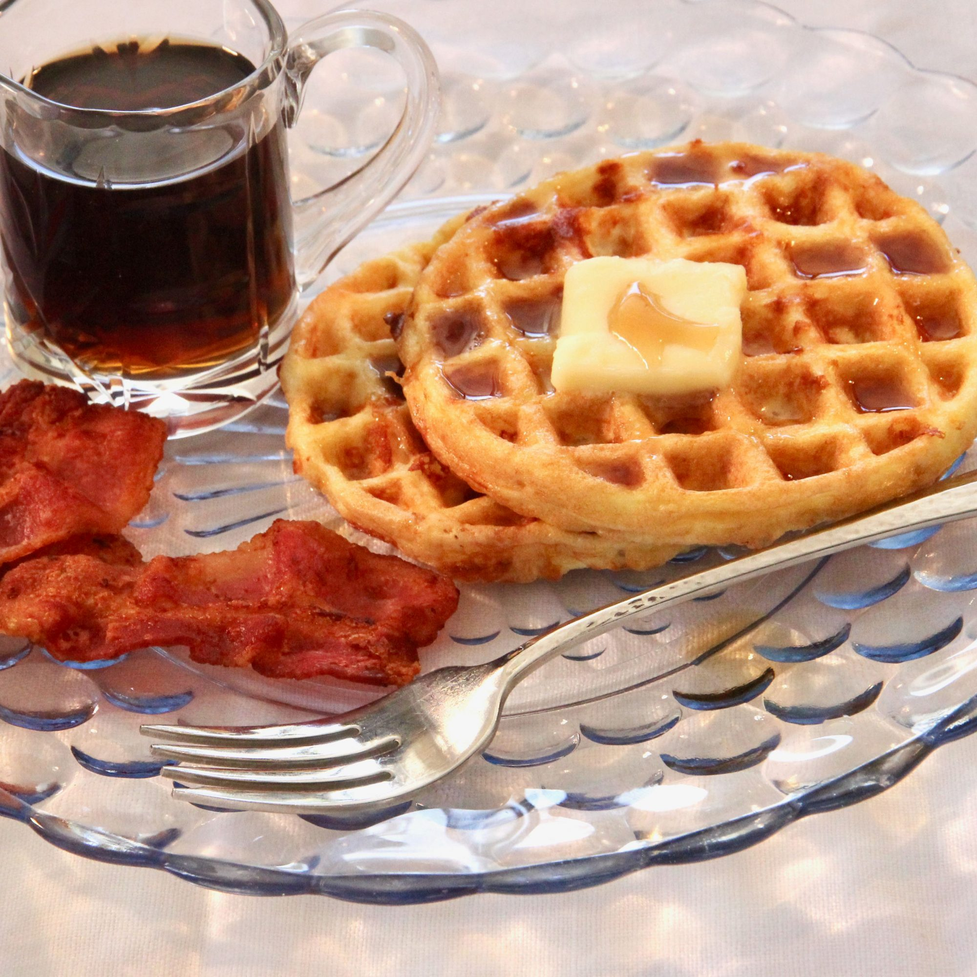 Chaffles on a glass plate with bacon