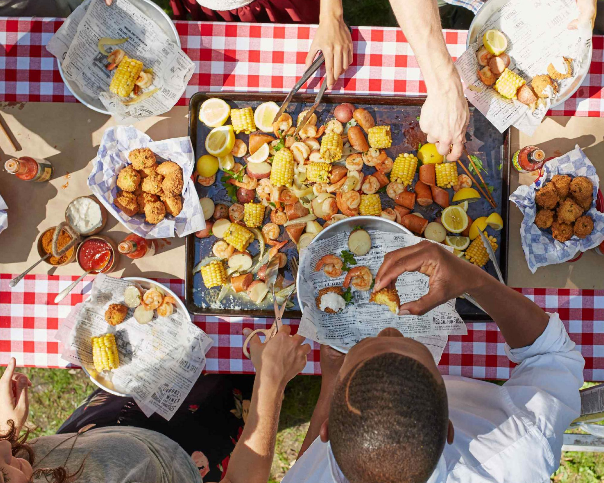 People reaching for shrimp boil on picnic table