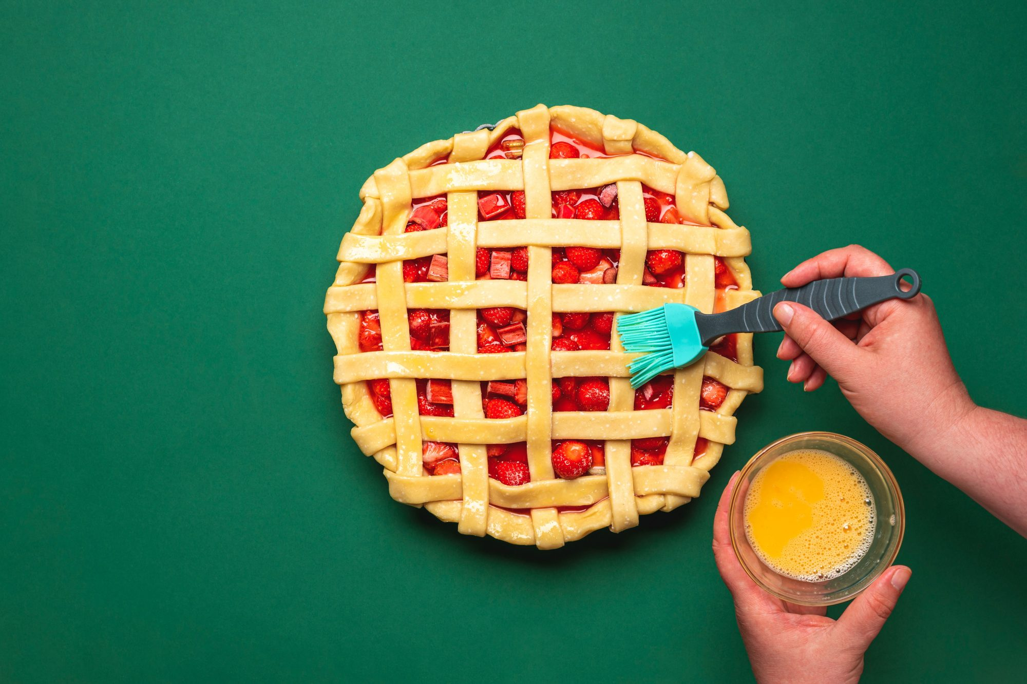 Person brushing egg wash onto pie
