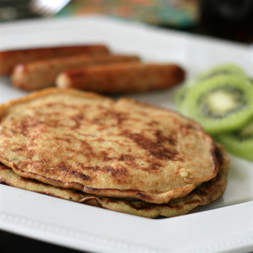 pancakes on a white plate with kiwi and sausage