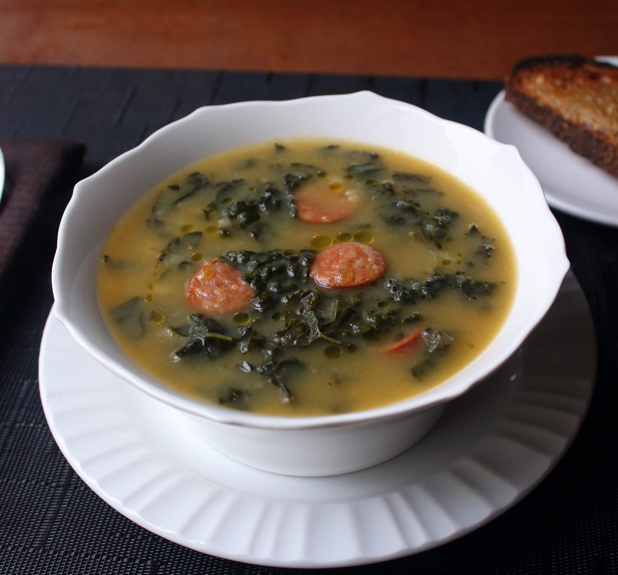 a bowl of kale soup with sliced sausage