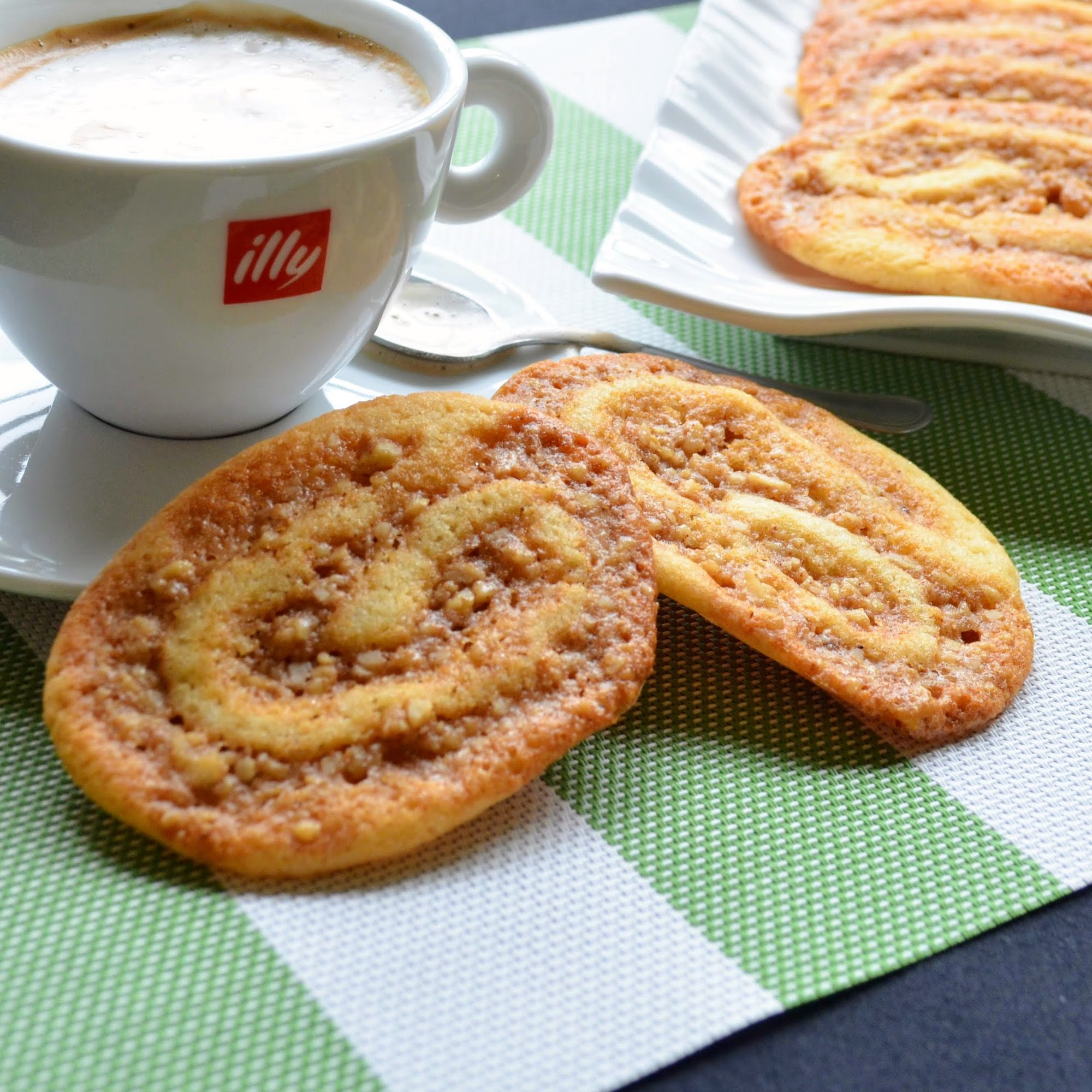 Baklava Pinwheel Cookies on a green and white placemat with a cappuccino