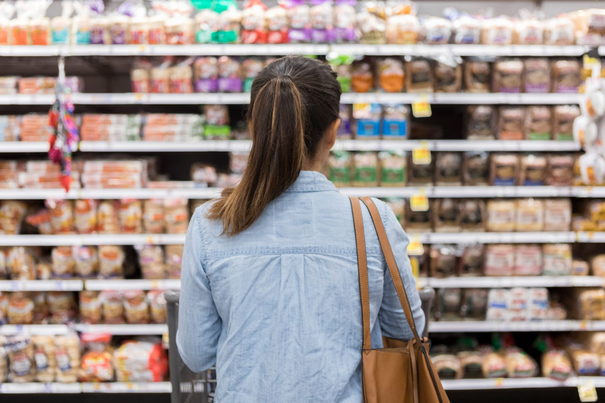 Unrecognizable woman marvels at grocery bread selection