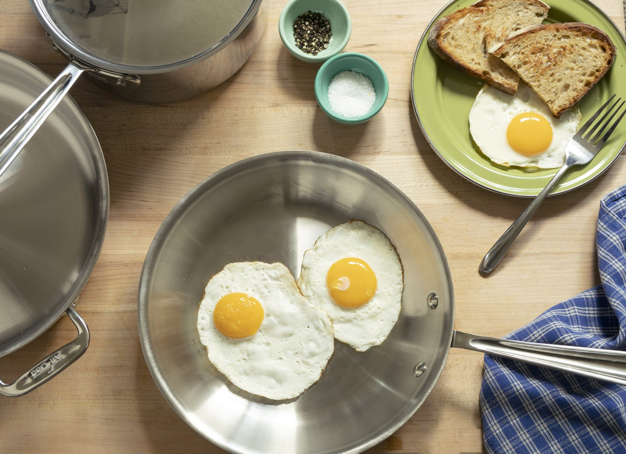 AllClad stainless steel cookware with fried eggs