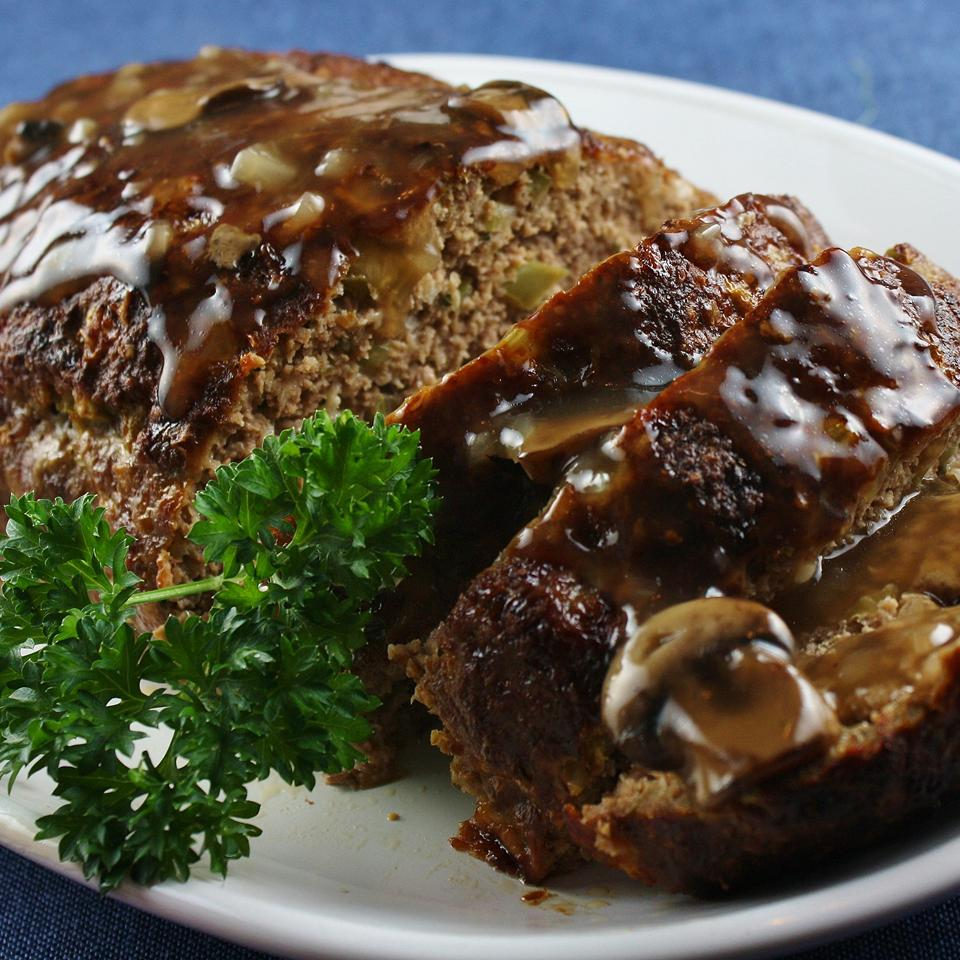 sliced glazed meatloaf on a white plate, garnished with a parsley sprig