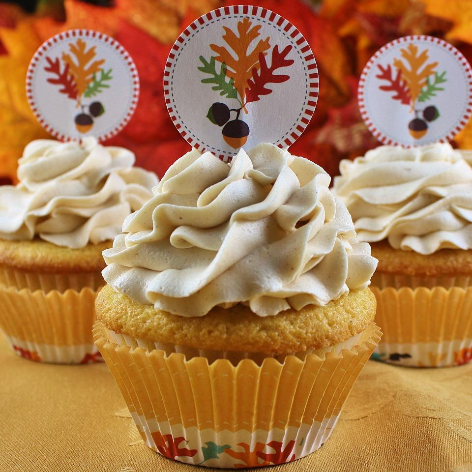 Cupcakes topped with a swirl of creamy frosting and fall-themed paper decorations